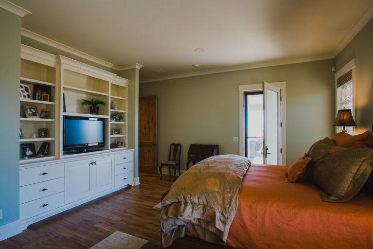 master bedroom, entertainment center, cabinetry, crown molding, hardwood flooring