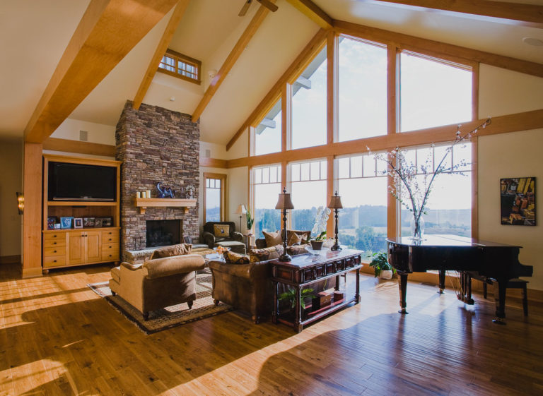 fireplace, stone, hardwood floor, entertainment center, ceiling beams, piano, fixed windows, dormer