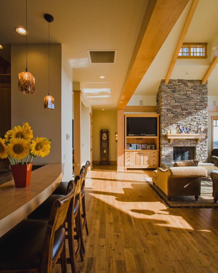 entertainment center, hardwood floor, stone fireplace, eating bar, pendant lighting