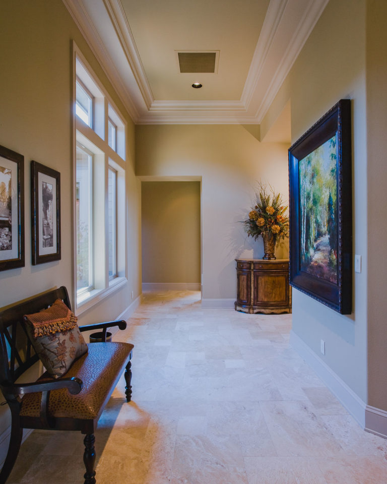 Travertine tile floor, crown mold, ceiling accent, casement window, baseboard