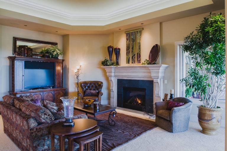 honed granite fireplace surround, paint grade mantel, accent lighting, crown mold, stepped ceiling